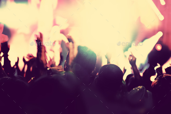 Concert, disco party. People with hands up in night club.