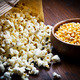 A bowl of popcorn and kernelson a wooden table - PhotoDune Item for Sale