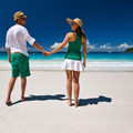 Couple in green walking on a beach at Seychelles - PhotoDune Item for Sale