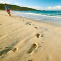 Woman at beautiful beach. Focus on footprints. - PhotoDune Item for Sale