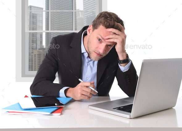 attractive businessman working in stress at office desk computer