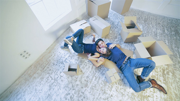 Couple Lying On The Floor Among The Boxes