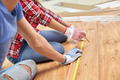 close up of couple with ruler measuring flooring - PhotoDune Item for Sale