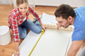 close up of couple measuring wallpaper - PhotoDune Item for Sale