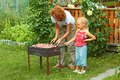 Little girl helping her mother to cook shish kebab - PhotoDune Item for Sale