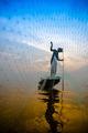 Silhouettes fisherman throwing fishing nets during sunset. - PhotoDune Item for Sale