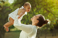 Mother Lifting Up And Turning Around Little Baby Daughter In Par - PhotoDune Item for Sale