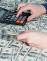 Man's hands with money and calculator