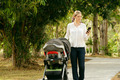 Mother With Baby In Pushchair Typing Message On Phone - PhotoDune Item for Sale