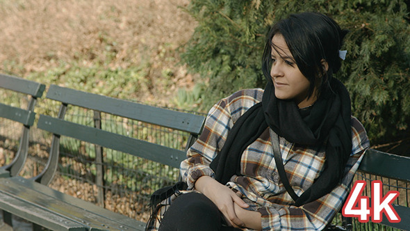 Girl Sitting on a Bench in Central Park Smiling