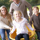 Family having fun with autumn leaves in garden - PhotoDune Item for Sale