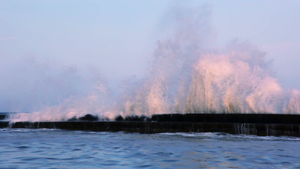 Surf Wave on the Breakwater at Sunset