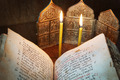 Orthodox religious still life with open ancient book and burning candles (focus on foreground) - PhotoDune Item for Sale