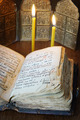 Orthodox religious still life with open old book and burning candles (focus on foreground) - PhotoDune Item for Sale
