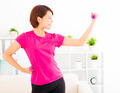 happy young woman exercising with dumbbells in living room - PhotoDune Item for Sale