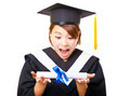 surprised young woman graduating holding diploma and looking - PhotoDune Item for Sale