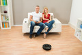 Couple With Remote Control And Robotic Vacuum Cleaner - PhotoDune Item for Sale