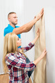 Young Couple Applying Wallpaper On Wall - PhotoDune Item for Sale