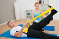 Female Instructor Helping Young Man While Exercising - PhotoDune Item for Sale
