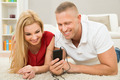 Couple With Mobile Phone Lying On Carpet - PhotoDune Item for Sale