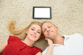 Couple With Digital Tablet Lying On The Carpet - PhotoDune Item for Sale