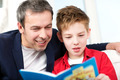Dad and son reading a book at home - PhotoDune Item for Sale