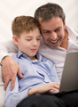 Happy dad and son with laptop at home - PhotoDune Item for Sale