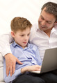 Father watching son working with laptop - PhotoDune Item for Sale