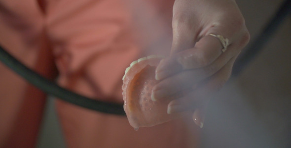 Dental Worker Cleaning Denture