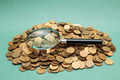 magnifying glass on a heap of coins - PhotoDune Item for Sale