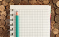 Notepad and pencil on a pile of coins - PhotoDune Item for Sale