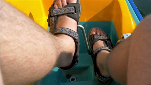 A Mans Feet Paddling the Water Bicyle