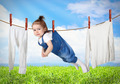Funny child hanging on line with clothes, laundry creative concept - PhotoDune Item for Sale
