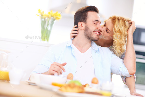 Woman giving good morning kiss to her husband
