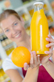 Shop assistant holding orange and juice - PhotoDune Item for Sale