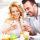 Happy couple eating breakfast and using smart phone - PhotoDune Item for Sale