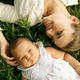 Mother With Caressing Baby Daughter Laying On Grass - PhotoDune Item for Sale