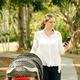 Mother With Baby In Pushchair Sending Message On Phone - PhotoDune Item for Sale