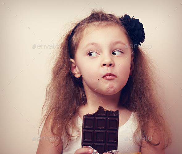 Thinking humor kid face eating chocolate. Closeup vintage
