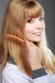 Closeup woman combing her hair with comb