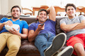 Group Of Men Sitting On Sofa Watching TV Together - PhotoDune Item for Sale