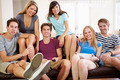 Group Of Friends Sitting On Sofa Watching TV Together - PhotoDune Item for Sale