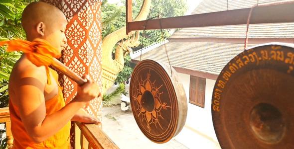 Buddhist Monk Hitting The Gong