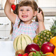 little cute girl holding and eating a strawberry in the kitchen - PhotoDune Item for Sale