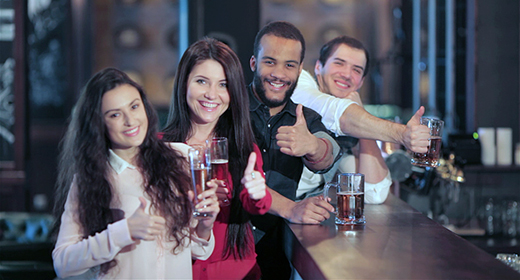 Company of guys and girl celebrating at the bar