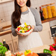Asian smiling woman with a colorful salad in her hands is standi - PhotoDune Item for Sale