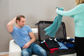 Man On Sofa While Woman Folding Clothes - PhotoDune Item for Sale