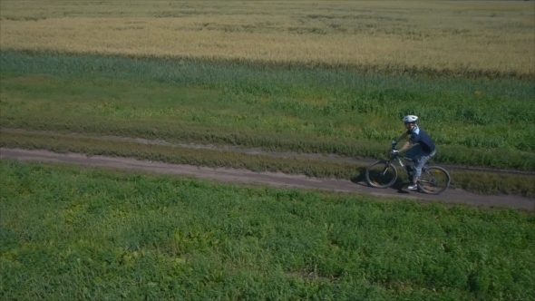 Man Cycling On a Rural Road Aerial View