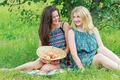 Two friends conversing under apple tree in summer garden - PhotoDune Item for Sale