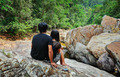 Young couple sitting on a rock by the stream in the tropical jun - PhotoDune Item for Sale